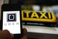 File illustration picture showing the logo of car-sharing service app Uber on a smartphone next to the picture of an official German taxi sign