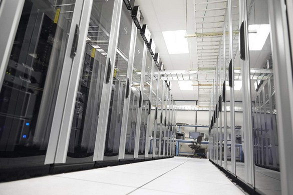 Empty hallway of a large corporate data center with rows of server racks with Dell enterprise products and an empty desk with Dell desktop computer.