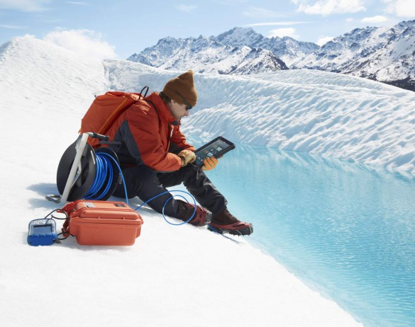 Man wearing sunglasses, protective jacket, gloves and cramp-on ice climbing shoes seated on a glacier holding a Dell Latitude 12 Rugged Tablet (Model 7202) computer. <a href=