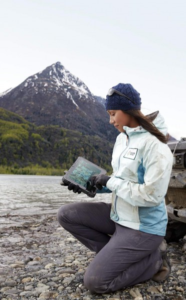 A woman in outdoor jacket and hat kneeling next to a river with a large mountain and forest in the background holding a Dell Latitude 12 Rugged Tablet (Model 7202) computer. A muddy vehicle can be seen in the background