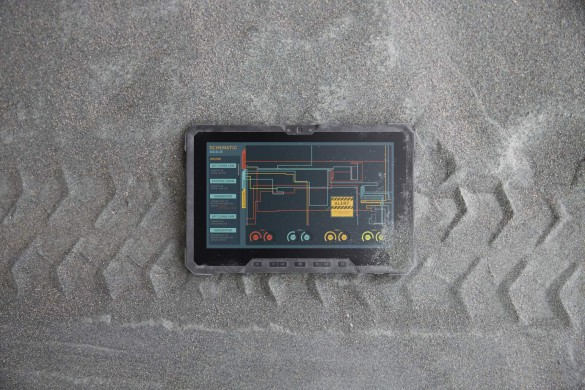 A Dell Latitude 12 Rugged Tablet computer (Model 7202) laying face-up on a gravel path with tire tracks beneath it.