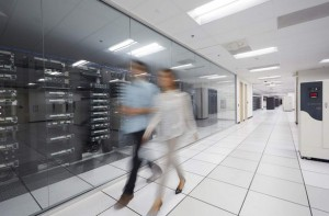 Male and female office workers walking together along the glass wall of an enclosed server room featuring open server racks, within a larger data center of Dell server products.