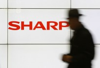 A pedestrian walks past a logo of Sharp Corp at a train station in Tokyo in this February 3, 2014 file photo. Embattled Japanese electronics maker Sharp Corp is preparing to seek aid from its two main lenders, a source with direct knowledge of the matter said, as it expects impairment losses from unprofitable businesses to mount this year.  REUTERS/Yuya Shino/Files (JAPAN - Tags: BUSINESS LOGO)