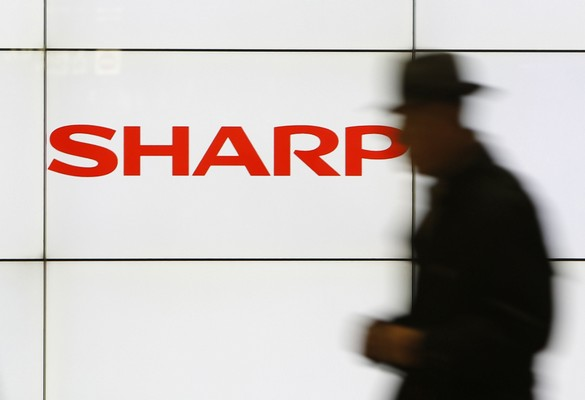 A pedestrian walks past a logo of Sharp Corp at a train station in Tokyo in this February 3, 2014 file photo. Embattled Japanese electronics maker Sharp Corp is preparing to seek aid from its two main lenders, a source with direct knowledge of the matter said, as it expects impairment losses from unprofitable businesses to mount this year. <a href=