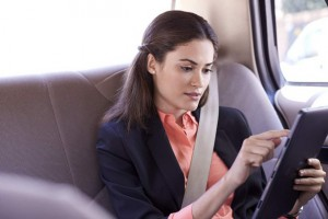Woman in Taxi Using Tablet