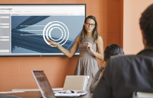 Businesswoman presenting a financial budget chart to colleagues in a conference room on a Dell 70 (Model C7016H) 70-inch conference room monitor