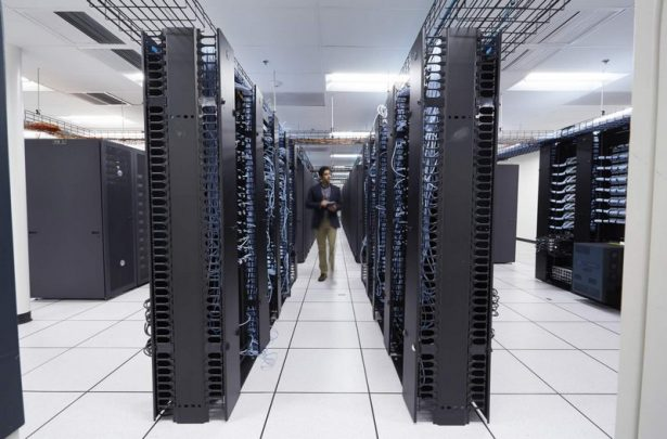 Man Walking in a Large Data Center, Using Venue Tablet