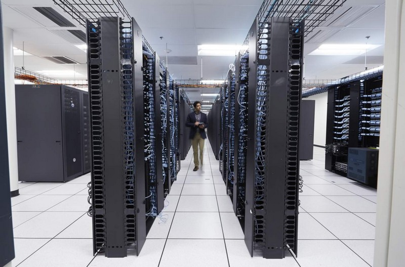 Male office worker walking between two rows of Dell server racks in a large data center, holding a Dell Venue 8 Pro 3000 Series (Model 3845, Bailey) tablet.