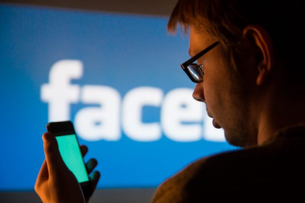 Man using Facebook application on smartphone