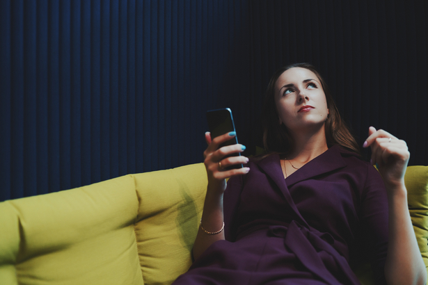 Businesswoman laying in office chillout and holding smartphone